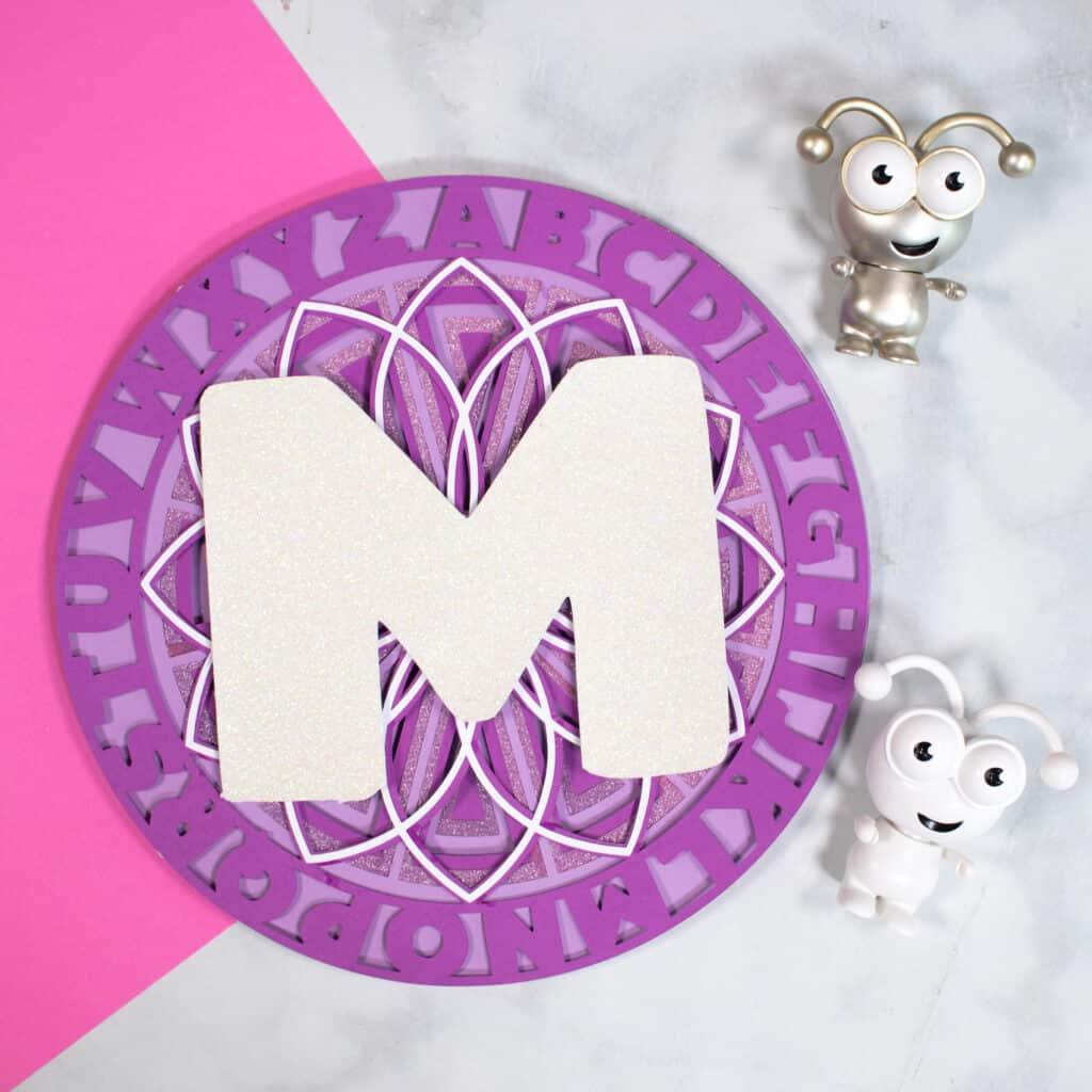 Alphabet Mandala vom beliebten US-Handwerksblog Sweet Red Poppy: Bild einer Frau, die ihr geschichtetes Alphabet-Mandala zusammenbaut.