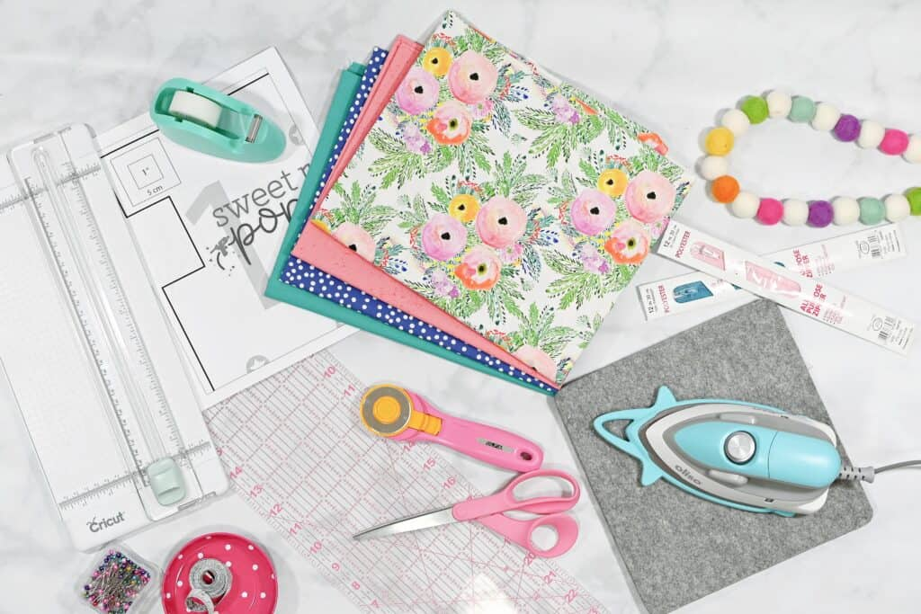 Supplies Needed for Your Box Zipper Pouch | Zippered Box Pouch by popular US sewing blog, Sweet Red Poppy: image of a rainbow felt ball garland, iron, pink sewing scissors, pink rotary cutter, fabric pins, Cricut cutter, blue scotch tape dispenser, and pink, blue, blue and white polka dot and floral fabric.