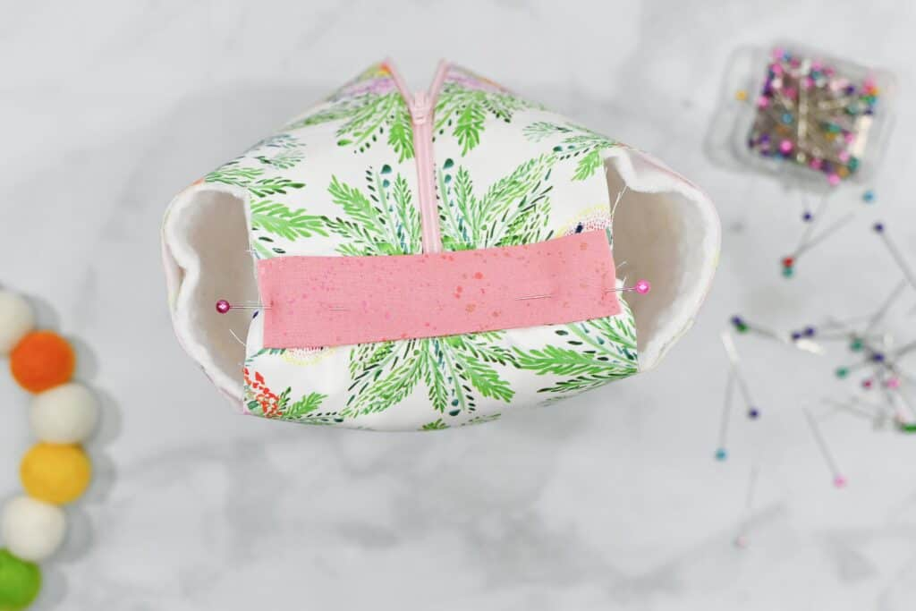 Zippered Box Pouch by popular US sewing blog, Sweet Red Poppy: image of pink fabric handles being pinned in place on a floral zippered box pouch.