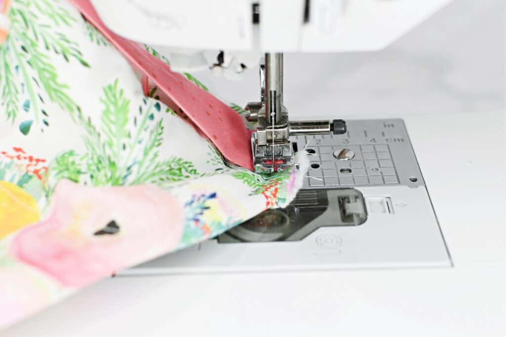 Zippered Box Pouch by popular US sewing blog, Sweet Red Poppy: image of a floral print zippered box pouch being sewn on a white sewing machine.