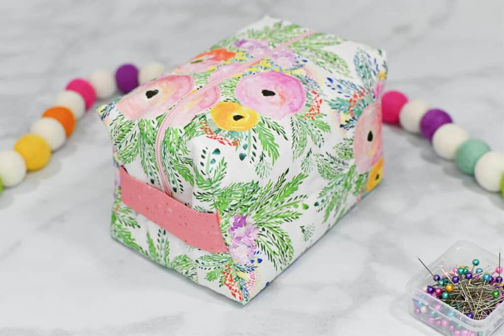Zippered Box Pouch by popular US sewing blog, Sweet Red Poppy: image of a floral print zippered box pouch next to a box of fabric pins and rainbow felt garland.