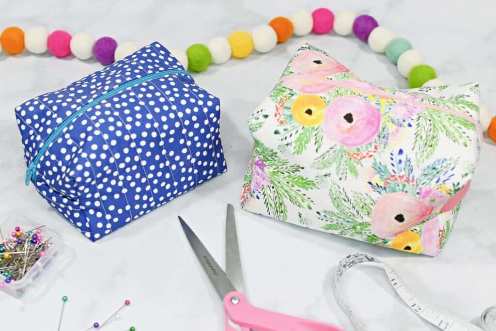 Zippered Box Pouch by popular US sewing blog, Sweet Red Poppy: image of a floral fabric zippered box pouch and a blue and white polka dot boxed pouch next to pink handle sewing scissors, a white fabric measuring tape, and fabric pins.