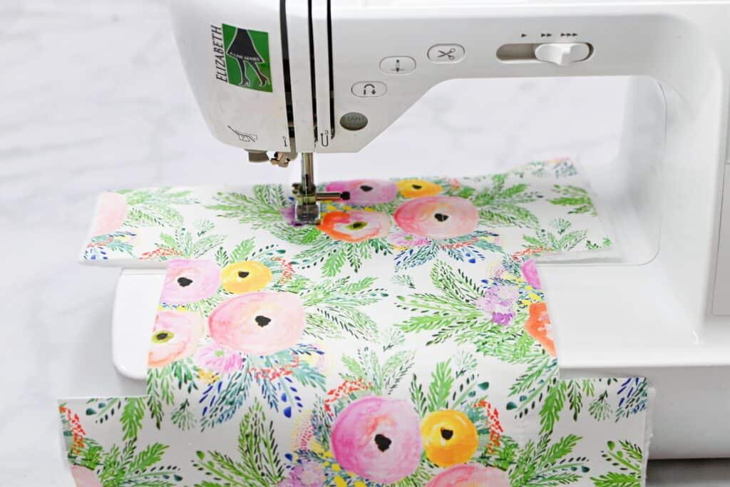 Zippered Box Pouch by popular US sewing blog, Sweet Red Poppy: image of floral fabric in a white sewing machine.