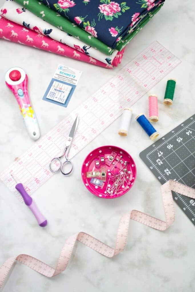 Sewing Supplies.  Serger VS Sewing Machine by popular US sewing blog, Sweet Red Poppy: image of fabric, rotary board, scissors, rotary cutter, needles, and a measuring tape.